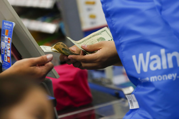 A customer receives cash change from a cashier at a Wal-Mart Stores Inc. location in the Porter Ranch neighborhood of Los Angeles, California, U.S., on Thursday, August 6, 2015. More U.S. parents are planning to increase back-to-school spending this fall than at any time in at least the past four years, according to a survey released Tuesday by the International Council of Shopping enters. Photographer: Patrick Fallon/Bloomberg via Getty Images